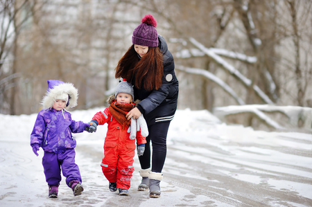 Young asian woman helping caucasian toddler boy anf girl with their winter clothes. Babysitting/childcarer concept. Banque d'images