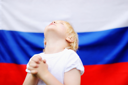 Portrait of emotional little boy with russian flag on background. Fans child supporting and cheering their national team at the sporting games