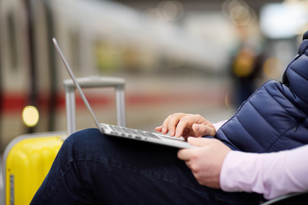 Freelancer working with a laptop in a train station while is waiting for transport. Middle age man on on railway station platform.