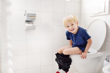 Cute little boy in restroom. Toddler child trainig use toilet. Hygiene for little child