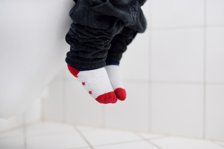 Close-up photo of little boy in restroom. Toddler child trainig use toilet. Hygiene for little child. Kids constipationdiarrhea concept Stock Photo