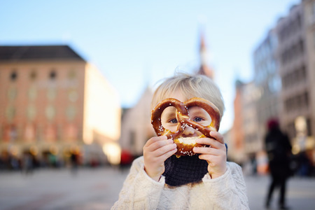 Little tourist holding traditional bavarian bread called pretzel on the town hall building background in Munich, Germany. Preschooler boy enjoy travel with his parents