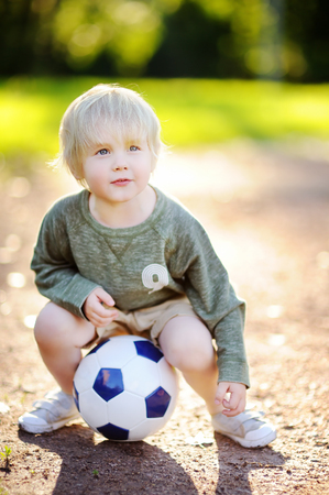 Little boy having fun playing a soccerfootball game on summer day. Active outdoors gamesport for children. Kids soccer classes and camps