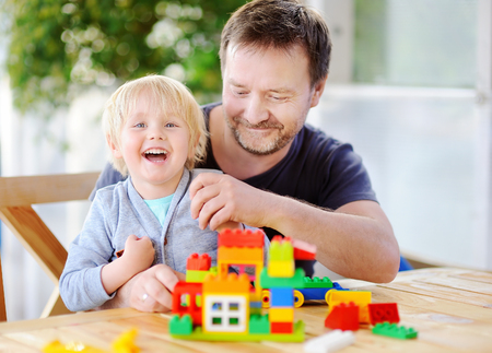 Little boy with his father playing with colorful plastic blocks at home. Development toys for preschooler children 版權商用圖片