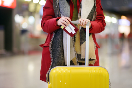 Close-up photo of woman with yellow suitcase holding passport and boarding pass at the international airport. Travel or immigration concept