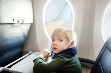 Charming kid traveling by an airplane. Afraid little boy sitting by aircraft window during the flight. Air travel with little kids
