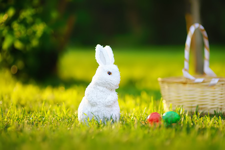 Colorful eggs and cute white toy bunny during egg hunt on Easter. Celebrating Easter outdoors. Accessories for Easter party in park
