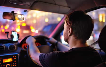 Male driver ride a car during evening traffic jam. Drive in the night city. Inside view.