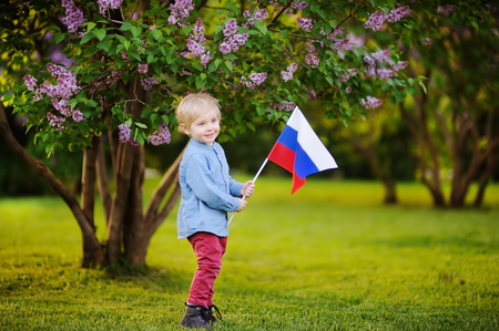 Cute little boy holding russian flag during walking in summer park Stock Photo