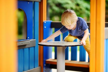 Little boy having fun on outdoor playground or in kindergarten. Sport activity leisure for kids.