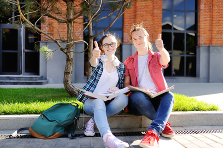 Young happy students with books and notes outdoors. Young couple show sight thumbs up and good luck. Smart young guy and girl in University campus. Learning and education for young people.