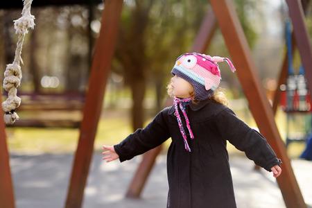 Little girl having fun on outdoor playground. Spring or autumn active sport leisure for kids. Kindergarten or school yard. Toddler child activity