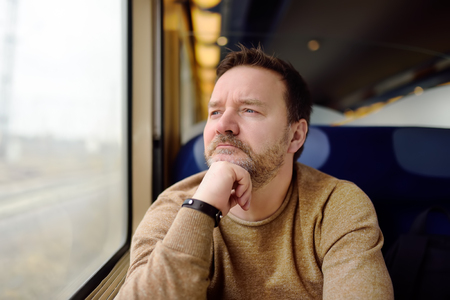 Middle age man looking out of the window of train. Passenger during travel by high speed express train in Europe