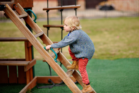Cute little boy having fun on outdoor playground. Spring/summer/autumn active sport leisure for kids. Outdoors wooden equipment for children game