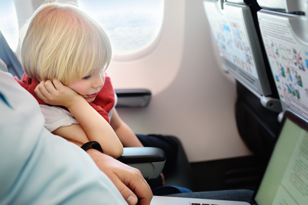 Portrait of little boy with his father during traveling by an airplane. Traveling with kids. Family enjoying trip in aircraft. Transportation safety