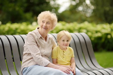 Schöne Oma und ihr kleines Enkelkind gehen zusammen im Park. Oma und Enkel