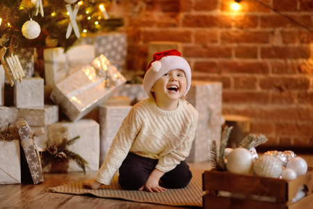 Cute little boy wearing Santa hat ready for celebrate holiday. Portrait of happy kid on Christmas eve. Cozy living room with decorated fir tree