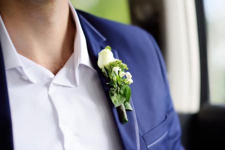 Nahaufnahmefoto des stilvollen Boutonniere-Bräutigams gemacht von den frischen Blumen. Detail des Hochzeitsanzugs des Bräutigams