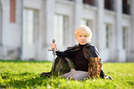 Portrait of a cute little boy dressed as a medieval knight with a sword and a shield. Medieval festival or costume party for kids Banco de Imagens