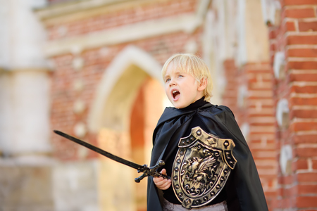 Porträt eines niedlichen kleinen Jungen, der als mittelalterlicher Ritter mit einem Schwert und einem Schild verkleidet ist. Mittelalterliches Fest oder Kostümparty für Kinder Standard-Bild