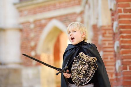 Portret van een schattige kleine jongen gekleed als een middeleeuwse ridder met een zwaard en een schild. Middeleeuws festival of verkleedfeest voor kinderen Stockfoto