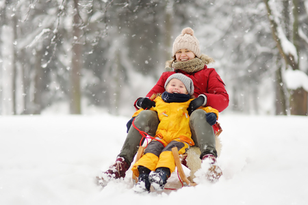 Little boy and mother sliding in the snow. Family winter activities outdoors.