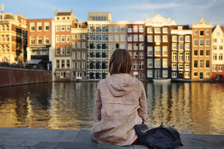 Young woman looking at the famous dancing houses of Amsterdam on sunny day, Netherlands