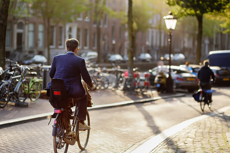 An elegantly dressed man rides a Bicycle in the center of Amsterdam. Bicycle capital of Europe. Фото со стока