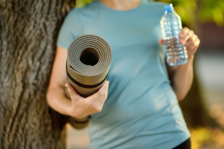 Woman with a yoga mat and bottle of water outdoors.Healthy lifestyle. Banque d'images