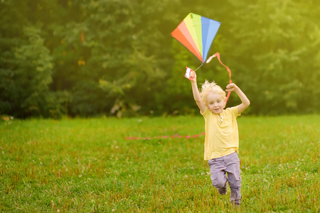 Little boy on a sunny day launches a flying kite. Outdoors summer activities for kids.