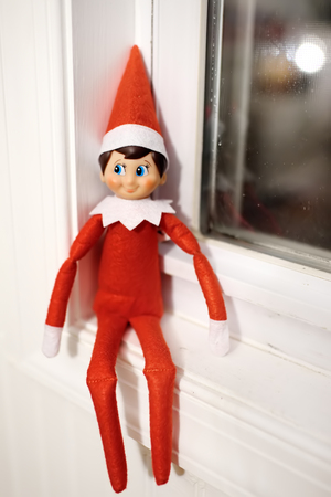 Funny Christmas toy elf on window. American christmas traditions. Xmas activities for family with kids.