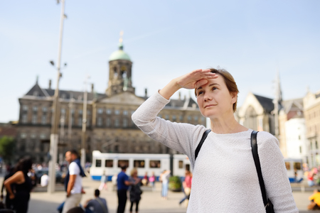 Mature woman standing on the Central dam square in the old city of Amsterdam. Travel to the most famous cities in Europe Stock Photo