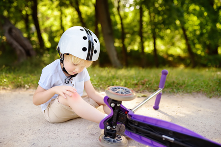 Toddler Boy In Safety Helmet Learning To Ride Scooter Little
