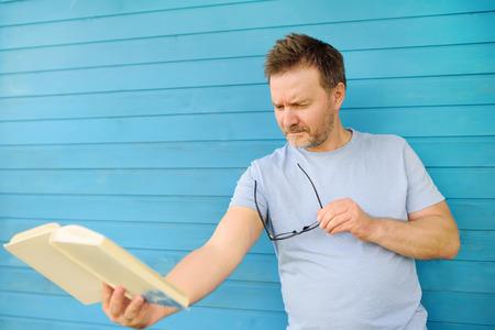 Porträt eines reifen Mannes mit großen schwarzen Augengläsern, der versucht, ein Buch zu lesen, aber aufgrund von Sehproblemen Schwierigkeiten hat, Text zu sehen. Weitsichtigkeit, Alterssichtigkeit.