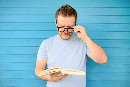 Portrait of mature man with big black eye glasses trying to read book but having difficulties seeing text because of vision problems. Problems disorder vision.