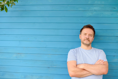 Shot of handsome mature man crossing hands and look at camera. Male portrait with blue wooden wall on background.