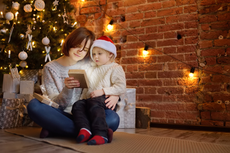 Mother with her little son reading a magic book in cozy living room. Family time on holidays