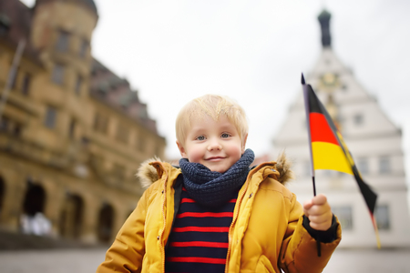 Little boy with a German flag on the square in Rothenburg Ob der Tauber. Small town of Deutschland. Travel in Germany/Bavaria.