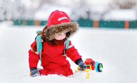 Little boy playing with bright car toy and fresh snow on a winter day