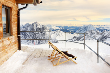 Sunbeds on the terrace of the Alpine Chalet house in the mountains. Winter vacation in Alps . Фото со стока