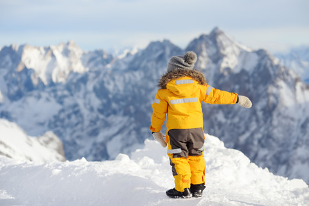 Little boy enjoying the view of the winter Alps mountains. Dangerous situations for little kids during winter vacation Stok Fotoğraf