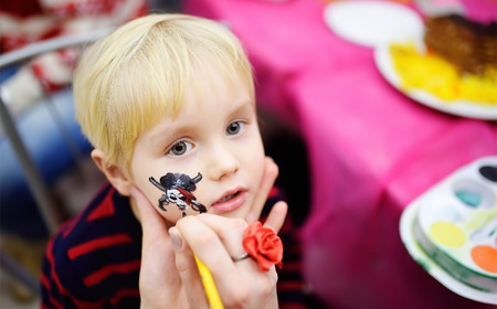 Face painting for cute little boy during kids merriment. Face paint for