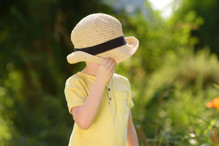 Little boy fooling around, covers his face with a straw hat. Fun for kids in the domestic garden at sunny summer day