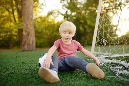 Little boy got injured playing football.Active outdoors gamesport for children. Kids soccer classes and camps. Safety concepts. Stock Photo