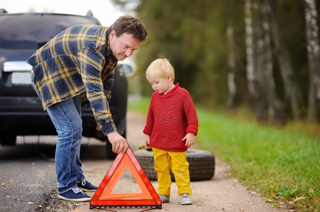 Father and his little son repairing car and changing wheel together on summer day. Family of two waiting car repair on the roadside