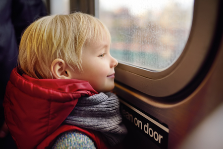 Little boy looks out the window of the car in the subway in new York. Family travel with children.