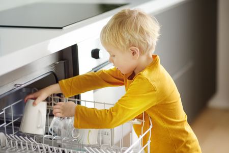 Child puts dirty crockery in the home dishwasher. Close-up. Moms little helper. 写真素材