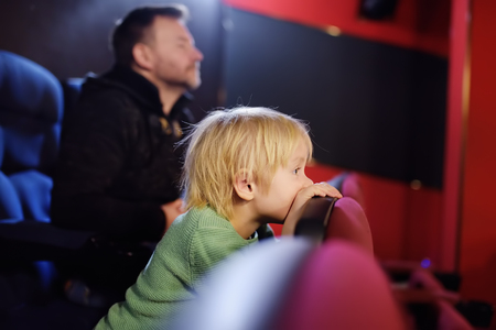 Cute little boy with his father watching cartoon movie in the cinema. Leisure/entertainment for family with kids. Banco de Imagens - 115768789