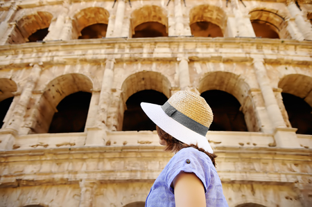 Young female traveler looking on famous the Colosseum in Rome. Sightseeing tour in Italy Фото со стока