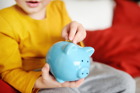 Little boy putting coin into piggy bank. Education of children in financial literacy.